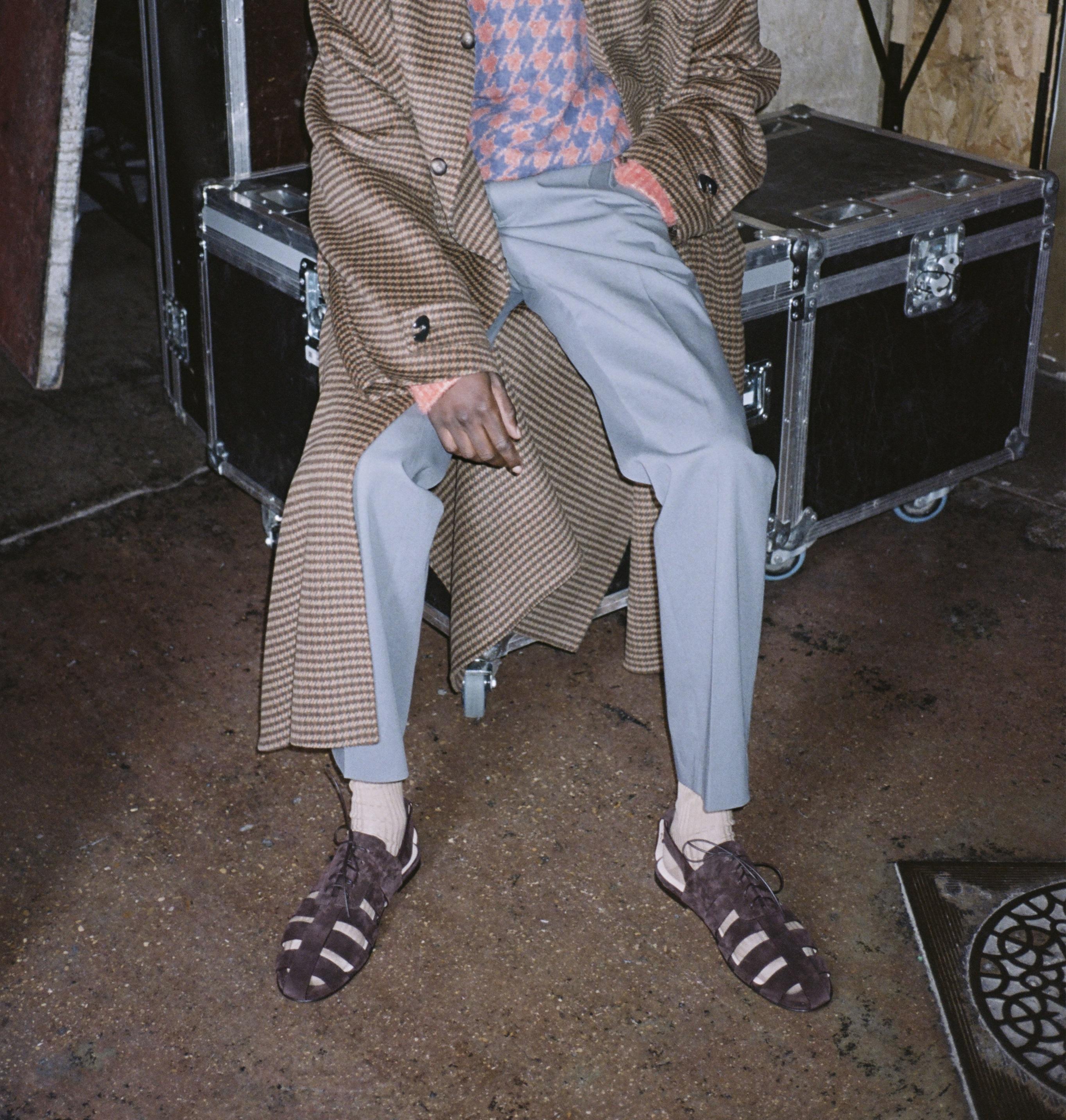 Frau sitzt auf Kiste, mit Cut-Out Schnürrschuhe und Oversized-Mantel