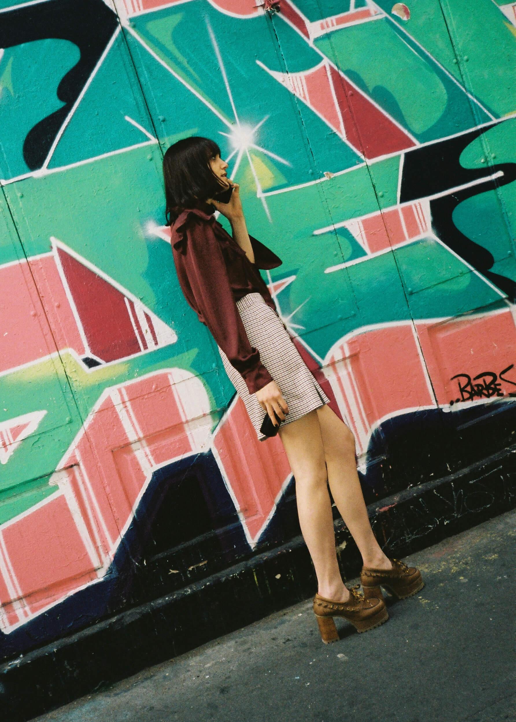 Model trägt See by Chloé Jupe und Bluse vor einer Graffitiwand