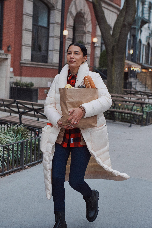 teaser Bild- Frau mit weissem Mantel trägt ihre Einkaufstüte