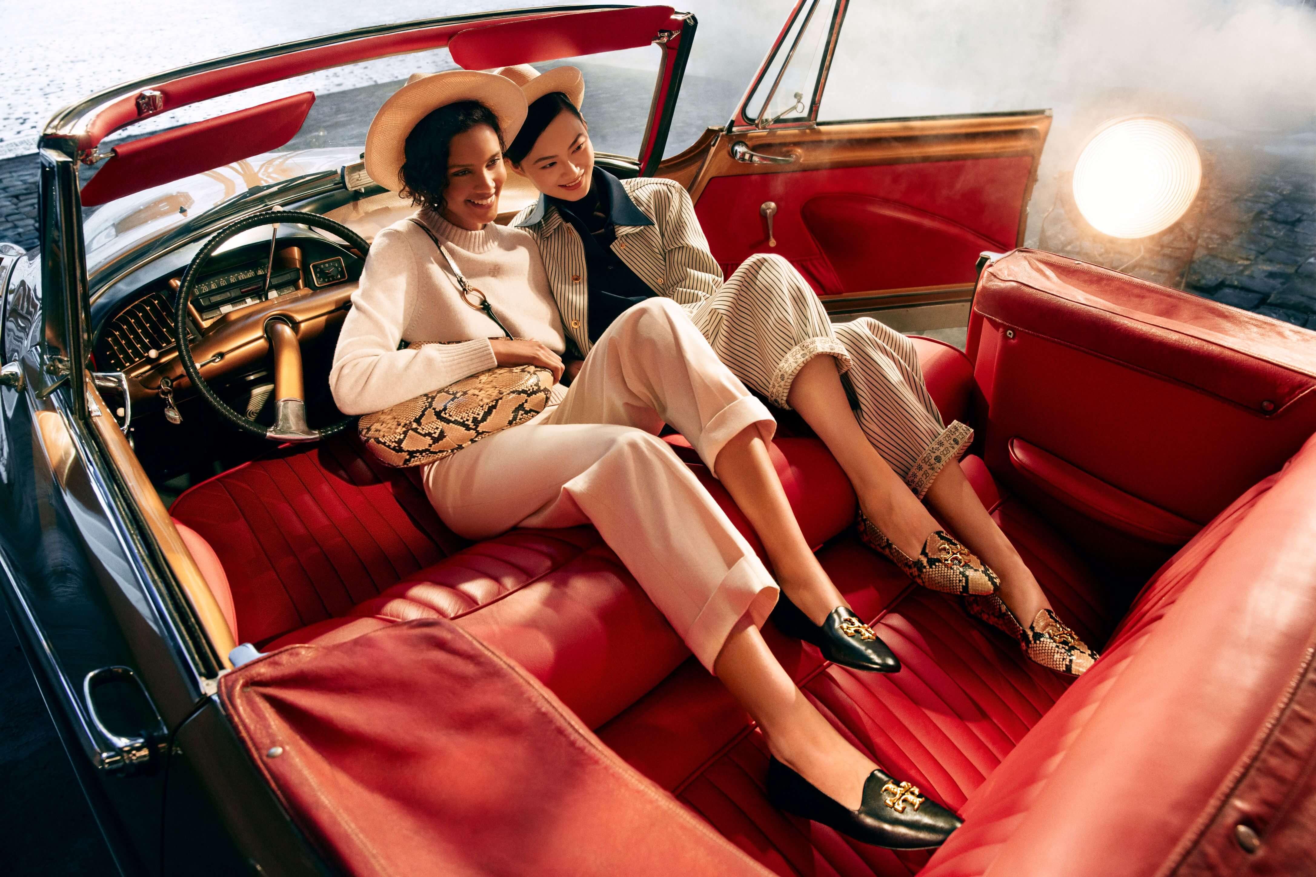 Zwei Models in einem Auto mit roten Ledersitzen tragen Tory Burch Outfits aus dem Jahr 2021