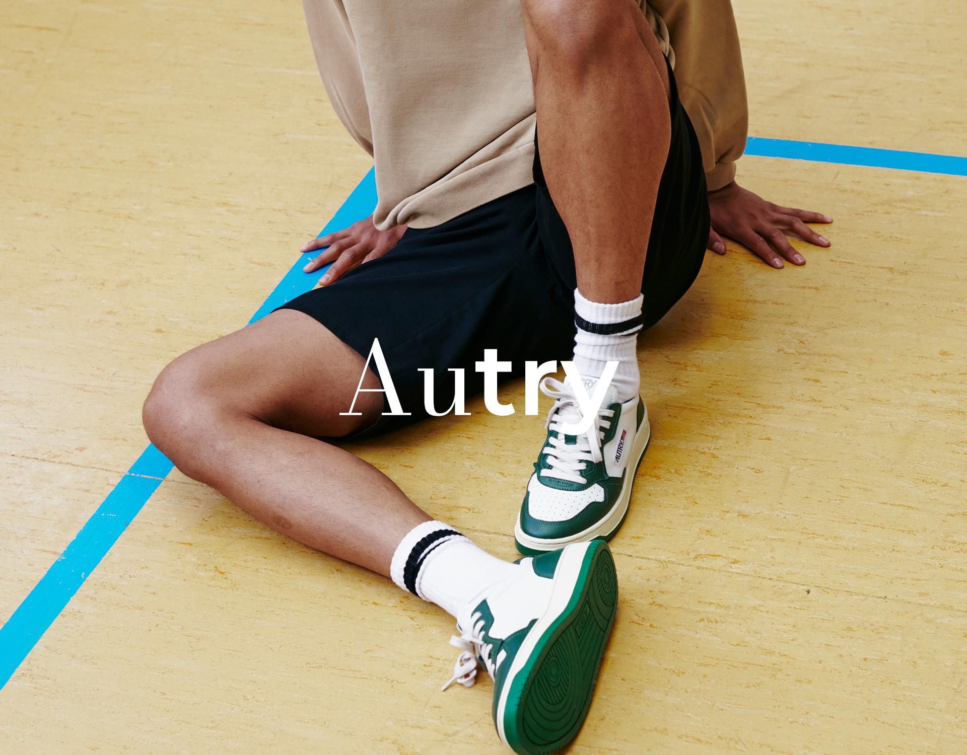 Mann sitzt in einer Turnhalle und trägt Autry Sneakers