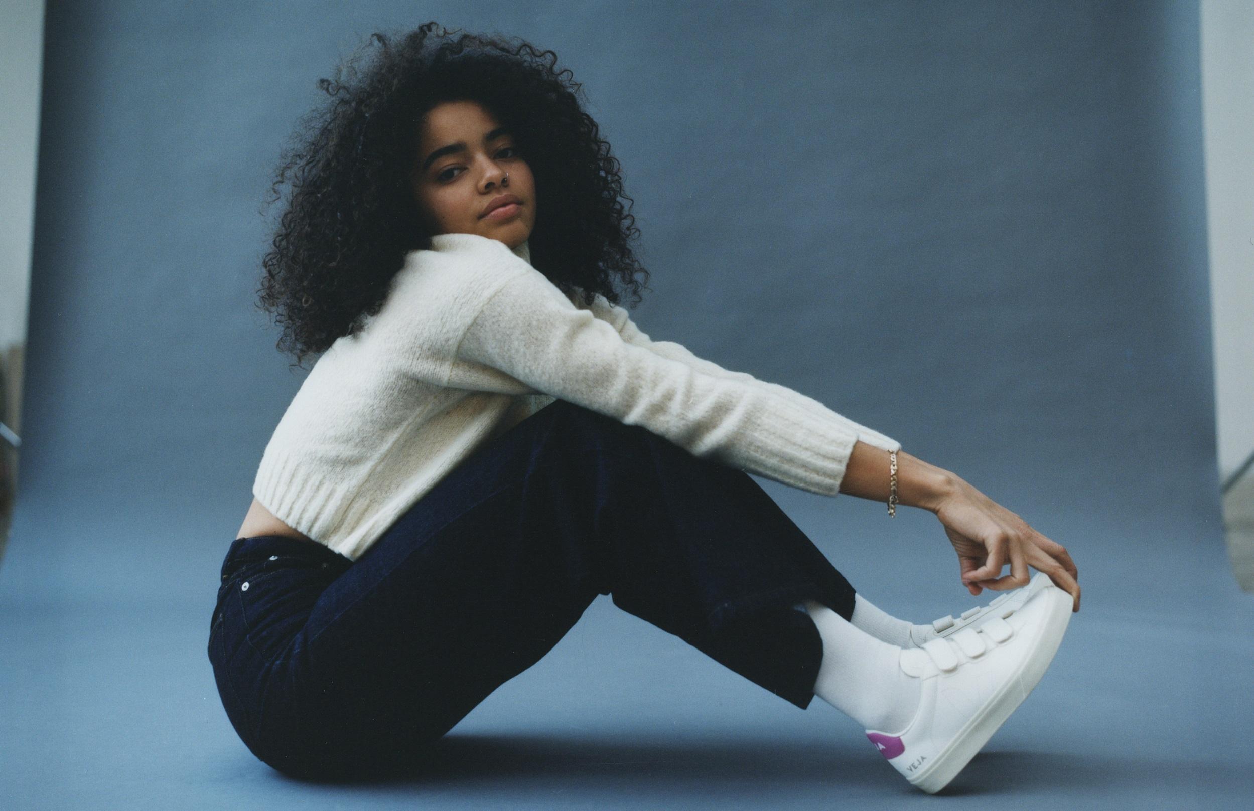 Model mit schwarzen Locken sitzt auf dem Boden und trägt Veja Sneakers aus der Kollektion 2021