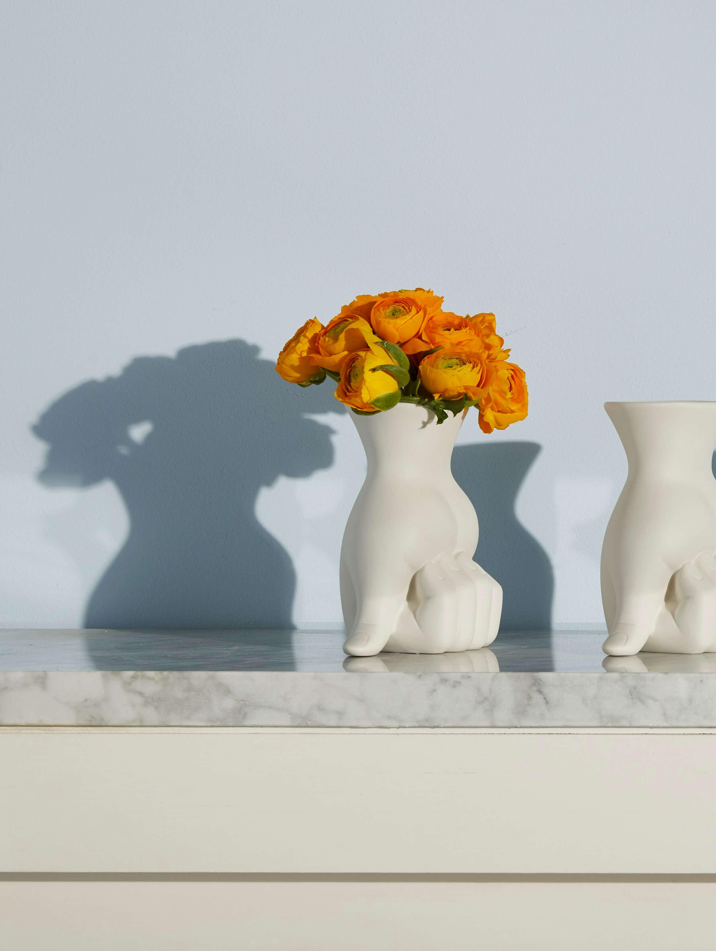 Zwei weisse Jonathan Adler Vasen mit orangen Blumen