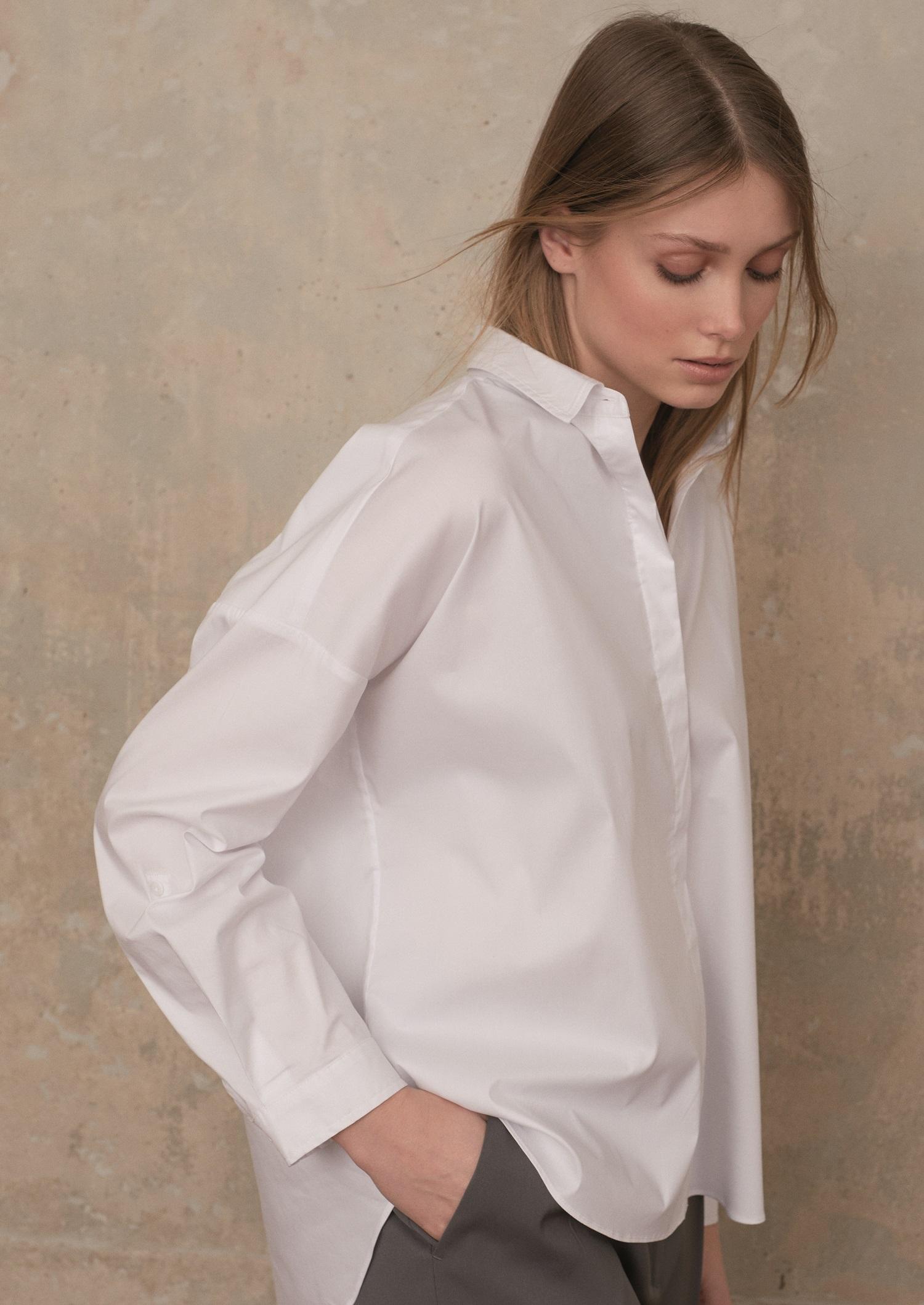 Model trägt weisse Oversized-Bluse