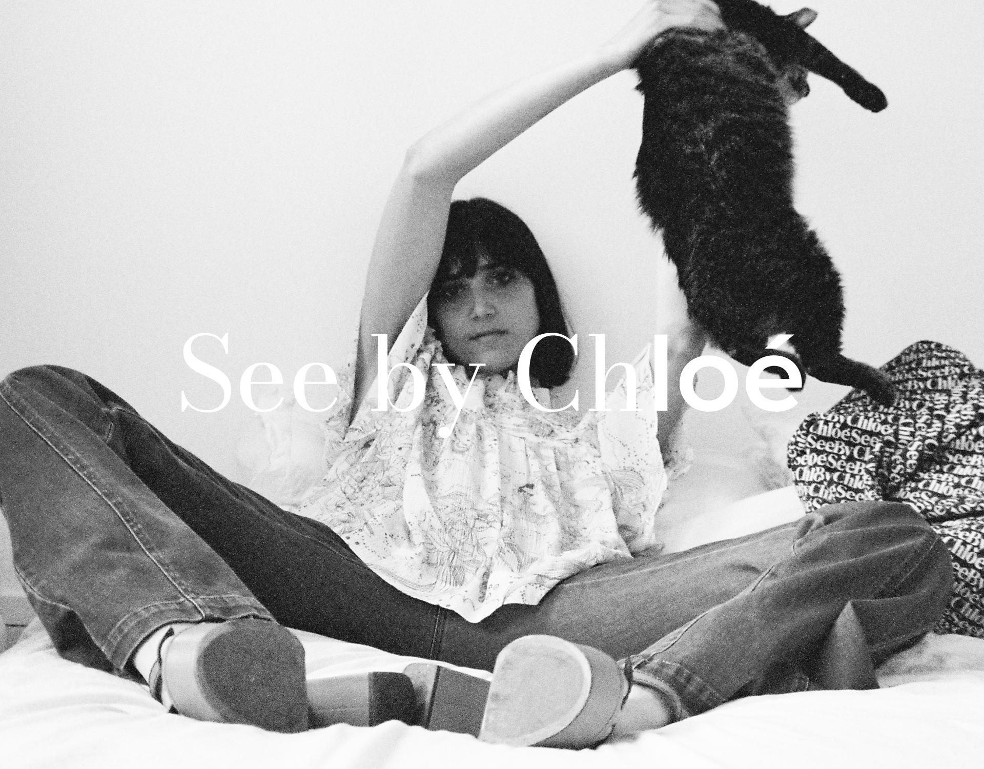 See by Chloé Model liegt auf Bett und hält eine Katze