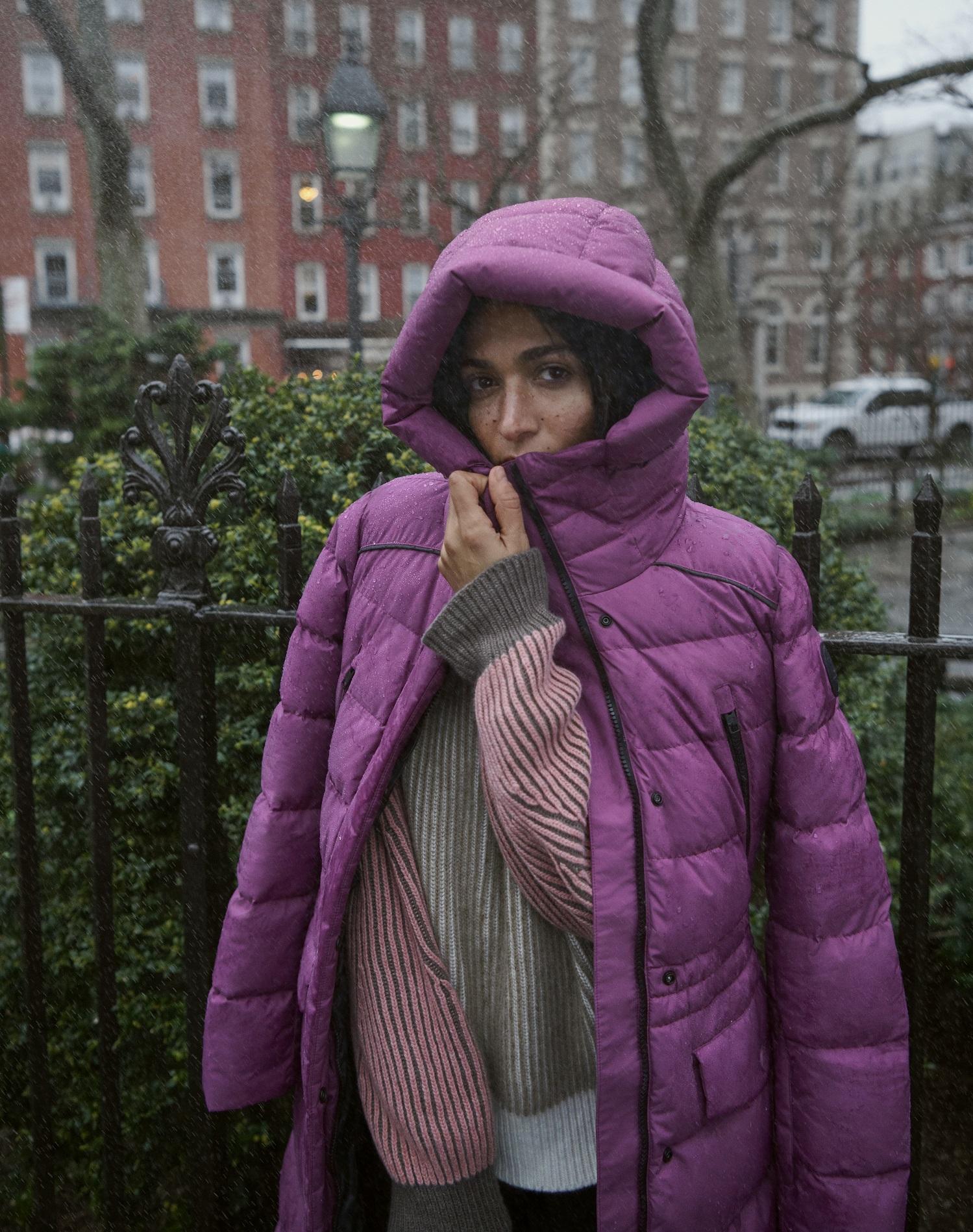 Frau hüllt sich in einen violetten Woolrich Daunenmantel