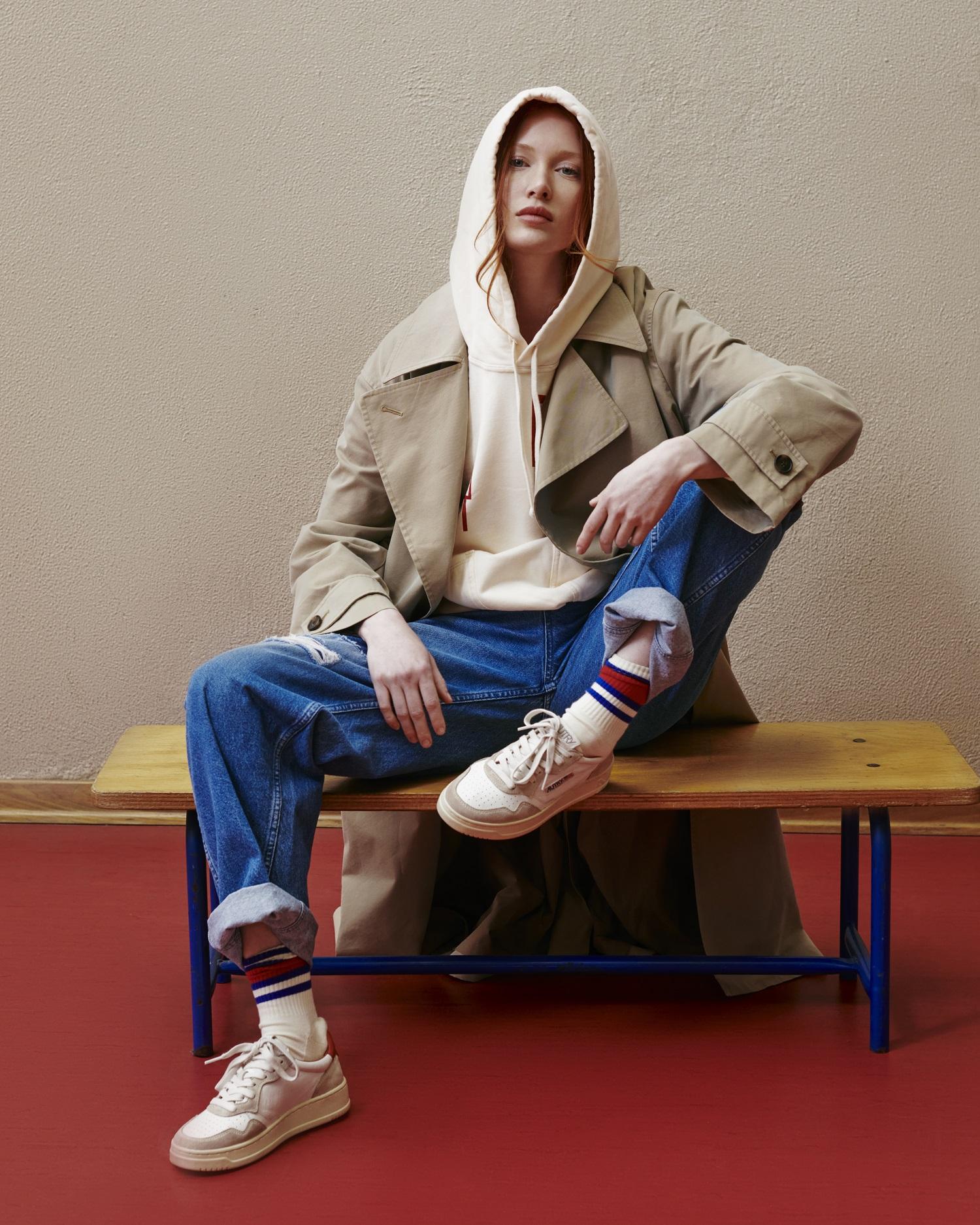 Model trägt Autry Sneakers und sitzt auf einer Holzbank