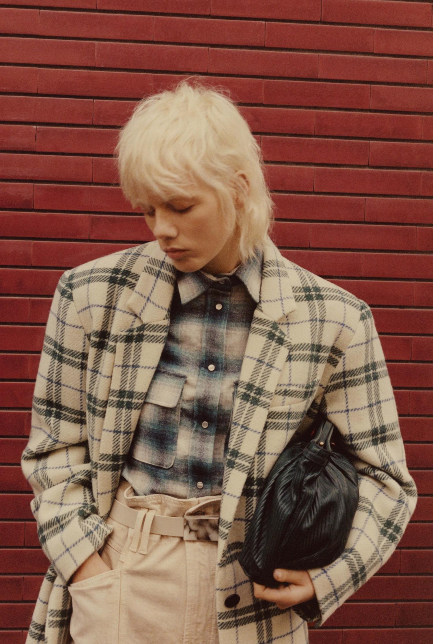 Model vor roter Ziegelsteinwand trägt Blazer und Handtasche von Isabel Marant Étoile.