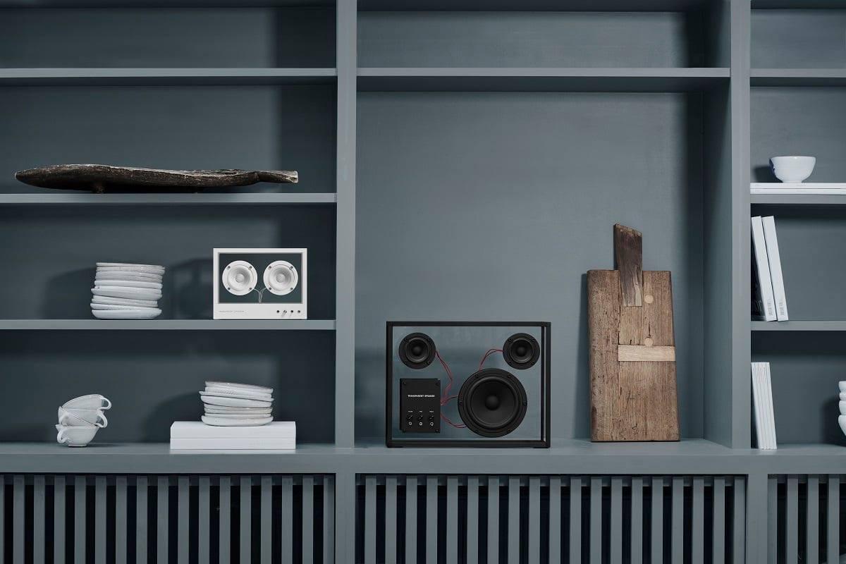Transparent Lautsprecher in schwarz und weiss in einem grauen Holzregal