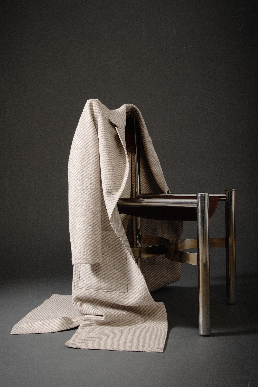 Mantel hängt über einen Stuhl vor grauem Hintergrund